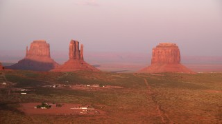 AX133_165 - 6K stock footage aerial video of flying past buttes in a desert valley, Monument Valley, Utah, Arizona, sunset