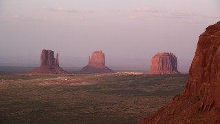 AX133_170 - 6K stock footage aerial video of flying by buttes and The View Hotel in famous Monument Valley, Utah, Arizona, sunset
