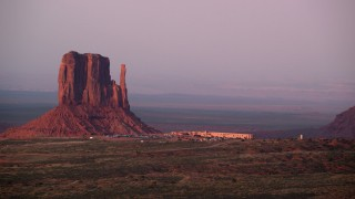 AX133_172 - 6K stock footage aerial video of lying by Mitten Butte and The View Hotel, Monument Valley, Utah, Arizona, sunset