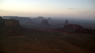 AX133_180 - 6K stock footage aerial video of flying by buttes and mesas in famous Monument Valley, Utah, Arizona, sunset