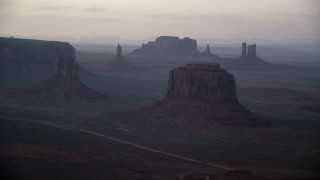 AX133_183 - 6K stock footage aerial video of passing West Mitten Butte, Merrick Butte in Monument Valley, Utah, Arizona, sunset