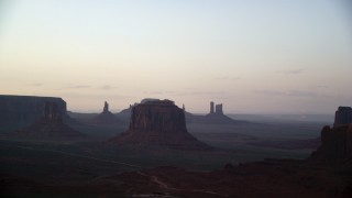AX133_191 - 6K stock footage aerial video of flying toward West Mitten Butte and Merrick Butte, Monument Valley, Utah, Arizona, sunset