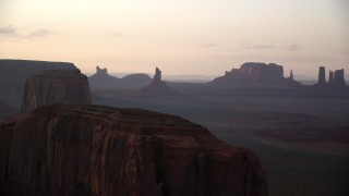 AX133_194 - 6K stock footage aerial video of flying by buttes in a hazy desert valley, Monument Valley, Utah, Arizona, sunset