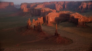 AX133_197 - 6K stock footage aerial video of Yei Be Chei Butte, Totem Pole Butte in Monument Valley, Utah, Arizona, sunset