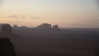AX133_206 - 6K stock footage aerial video of a group of buttes in a hazy desert valley, Monument Valley, Utah, Arizona, twilight