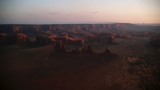 AX133_208 - 6K stock footage aerial video of passing by buttes, rock formations and mesa in Monument Valley, Utah, Arizona, twilight