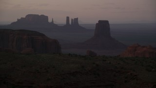 AX133_214 - 6K stock footage aerial video of flying by East Mitten Butte, Elephant Butte in Monument Valley, Utah, Arizona, twilight