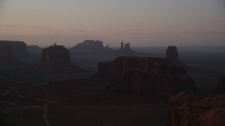 AX133_215 - 6K stock footage aerial video of buttes in a hazy valley, Monument Valley, Utah, Arizona, twilight