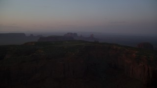 AX133_222 - 6K stock footage aerial video of Mitchell Mesa and distant buttes, Monument Valley, Utah, Arizona, twilight