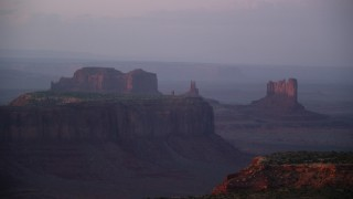 AX133_224 - 6K stock footage aerial video of mesas and buttes in the hazy valley, Monument Valley, Utah, Arizona, twilight