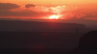 AX134_005 - 6K stock footage aerial video of a view of the setting sun beyond buttes and mesa, Monument Valley, Utah, Arizona, sunset