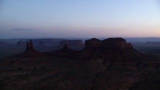 AX134_018 - 6K stock footage aerial video of a view of buttes through hazy Monument Valley, Utah, Arizona, twilight