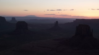 AX134_031 - 6K stock footage aerial video of flying by three desert buttes, Monument Valley, Utah, Arizona, twilight