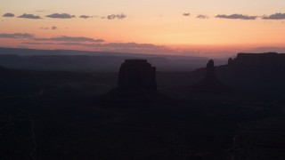 AX134_033 - 6K stock footage aerial video of passing by Merrick Butte, West Mitten Butte in Monument Valley, Utah, Arizona, sunset