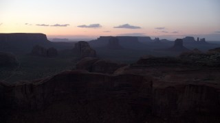 AX134_038 - 6K stock footage aerial video of passing desert buttes and mesas in Monument Valley, Utah, Arizona, twilight