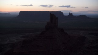 AX134_062 - 6K stock footage aerial video of flying by Big Indian Butte in Monument Valley, Utah, Arizona, twilight