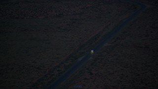 AX134_068 - 6K stock footage aerial video of tracking SUV on highway in desert valley, Monument Valley, Utah, Arizona, twilight