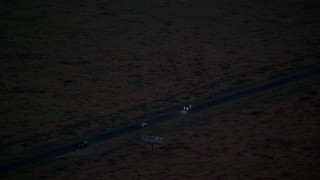AX134_069 - 6K stock footage aerial video track SUV on highway in desert, Monument Valley, Utah, Arizona, twilight