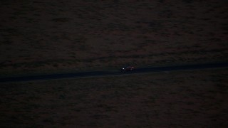 AX134_070 - 6K stock footage aerial video of tracking SUV on highway in Monument Valley, Utah, Arizona, twilight
