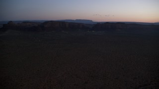 AX134_071 - 6K aerial stock footage video of flying by small town and Oljeto Mesa in Goulding, Utah, twilight