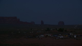 AX134_075 - 6K stock footage aerial video of flying by small town and buttes in Monument Valley, Utah, Arizona, night