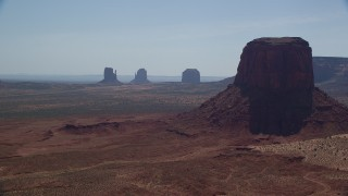 AX135_007 - 6K stock footage aerial video of flying by buttes in hazy desert valley, Monument Valley, Utah, Arizona, sunset