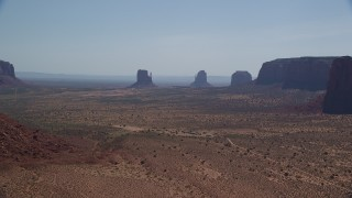 AX135_009 - 6K stock footage aerial video of a wide view of buttes in a hazy desert valley, Monument Valley, Utah, Arizona
