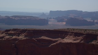 AX135_012 - 6K stock footage aerial video fly over Mitchell Mesa, and approach mesas, buttes in Monument Valley, Utah, Arizona
