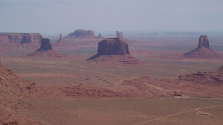 AX135_019 - 6K stock footage aerial video of a wide view of flying by buttes and hazy desert, Monument Valley, Utah, Arizona