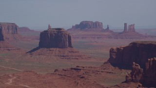 AX135_020 - 6K stock footage aerial video flying by Merrick Butte, Camel Butte, Elephant Butte in Monument Valley, Utah, Arizona