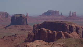 AX135_021 - 6K stock footage aerial video flyby Merrick Butte, Camel Butte, Elephant Butte, with buttes and mesas in distance, Monument Valley, Utah, Arizona