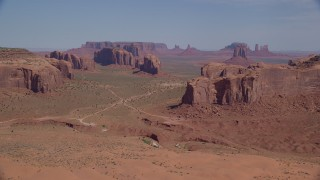 AX135_026 - 6K stock footage aerial video of flying by numerous buttes and mesas in a desert valley, Monument Valley, Utah, Arizona