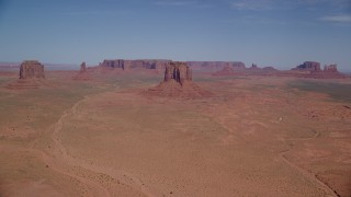 AX135_035 - 6K stock footage aerial video of a wide view of several buttes and mesas in a desert valley, Monument Valley, Utah, Arizona