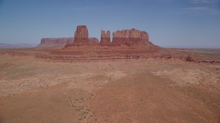 AX135_044 - 6K stock footage aerial video of flying toward buttes surrounded by desert valley, Monument Valley, Utah, Arizona
