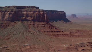 AX135_055 - 6K stock footage aerial video of a reverse view of Eagle Rock Butte by Eagle Mesa, Monument Valley, Utah, Arizona