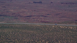 AX135_066 - 6K stock footage aerial video of tracking car traveling on Highway 163 in Monument Valley, Utah, Arizona