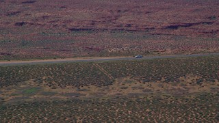 AX135_068 - 6K stock footage aerial video of a car slowing to a stop on Highway 163, Monument Valley, Utah, Arizona