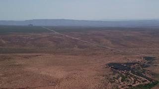 AX135_070 - 6K stock footage aerial video of approaching Highway 163 through desert valley, Monument Valley, Utah, Arizona
