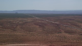 AX135_072 - 6K stock footage aerial video of an approach to Highway 163 in a desert valley, Monument Valley, Utah, Arizona