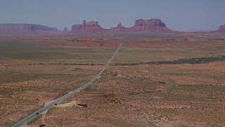 AX135_076 - 6K stock footage aerial video of flying over Forrest Gump Point by Highway 163, approach distant buttes in Monument Valley, Utah, Arizona