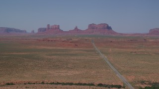 AX135_078 - 6K stock footage aerial video of passing by distant buttes, seen from Highway 163, Monument Valley, Utah, Arizona