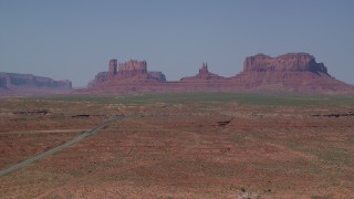 AX135_080 - 6K stock footage aerial video of a wide view of Highway 163 leading to desert buttes, Monument Valley, Utah, Arizona