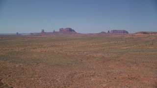AX135_084 - 6K stock footage aerial video of a wide view of distant buttes in an open desert valley, Monument Valley, Utah, Arizona