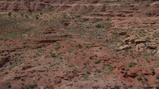 AX135_087 - 6K stock footage aerial video of flying low over desert while approaching a butte, Monument Valley, Utah, Arizona