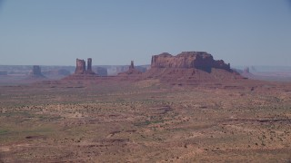 AX135_090 - 6K stock footage aerial video of flying toward several buttes across hazy desert valley, Monument Valley, Utah, Arizona