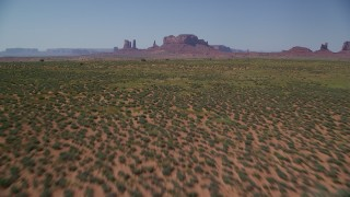 AX135_093 - 6K stock footage aerial video of flying low over desert, tilt to reveal buttes in the distance, Monument Valley, Utah, Arizona