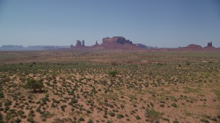 AX135_094 - 6K stock footage aerial video of approaching buttes across desert valley, Monument Valley, Utah, Arizona
