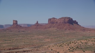 AX135_103 - 6K stock footage aerial video of flying by buttes, with Highway 163 in the foreground, Monument Valley, Utah, Arizona