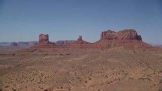 AX135_106 - 6K stock footage aerial video of an approach to buttes across a desert valley, Monument Valley, Utah, Arizona