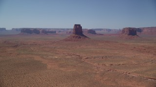 AX135_113 - 6K stock footage aerial video of an approach to East Mitten Butte in a desert valley, Monument Valley, Utah, Arizona